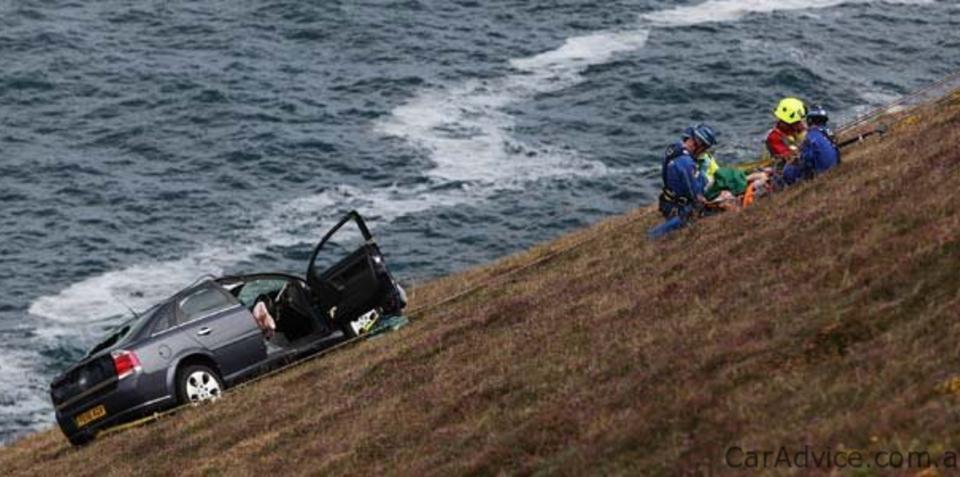 UK driver clings to cliff edge after rolling car